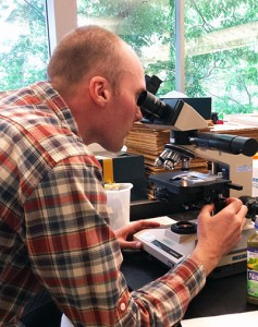 """Robin Sleith uses a compound microscope to look for algae in Naked """"Green Machine"""" juice."""