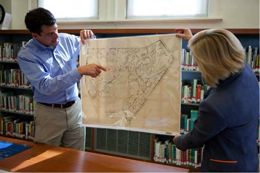 Todd Forrest and Vanessa Sellers hold up the Garden's first detailed, general survey map of 1896.