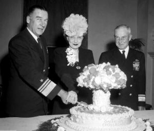 Operation Crossroads commanding officer Vice Admiral William Blandy and his wife slice into an Operation Crossroads cake following the first Bikini Atoll nuclear tests in 1946.