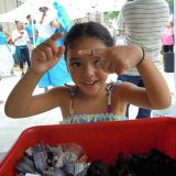 Little girl holding a worm at an event for Bronx Green Up.
