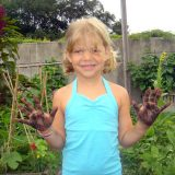 Little girl holding her hands up with dirt on them from the family garden