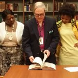 Image of a Library professional showing a book to students.