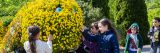 Children looking at a sculpture of a caterpillar with yellow flowers