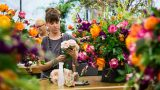Photo of a woman creating a bouquet in a Floral Design class
