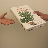 Photo of one person handing a book to another person