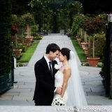 Bride and Groom taking a photo in the rose garden