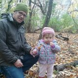 A child and her grandfather standing in leaves.