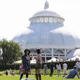 Two visitors enjoy an event outside the Enid A. Haupt Conservatory.