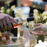 Wine is poured into a glass in front of a backdrop of iced wine bottles and daffodils.
