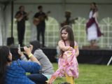 Little girl dancing with face paint on in front of a band.