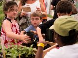 young boy and girl potting up a plant