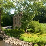 Summer image of the Stone Mill from the bridge over the Bronx River.
