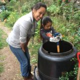 BGU Staff showing a small girl how to compost in a bin.
