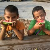 Two young boys enjoying watermelon from a community garden