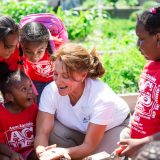 Volunteer working with kids in the family garden.