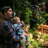 A father holding his child at the Holiday Train Show.