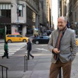 NYBG poet laureate Billy Collins standing on a busy New York City street.