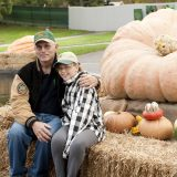 Photo of a man and a child next to a giant pumpkin