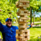 man in blue shirt playing a game of jenga