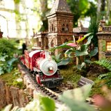 Red train passing through buildings in the Holiday Train Show.