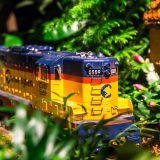 Photo of a model train surrounded by plants
