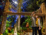 A couple taking a picture in front of a bridge at the Holiday Train Show.