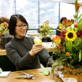 A woman working on a seasonal centerpiece
