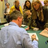 An author signing a book at a Booksigning