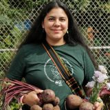 A woman holding vegetables harvested from a community garden.