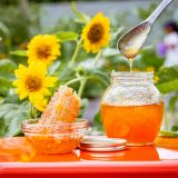 Image of honey in a jar with sunflowers