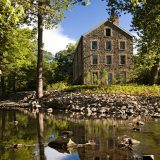An old mill building made from stone with ten windows stands on a rocky river bank with a single, thin tree in the foreground and others in the background.