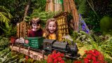 Two kids looking at a model train during the Holiday Train Show in the Conservatory