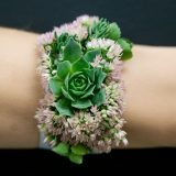a bracelet made out of succulents and flowers
