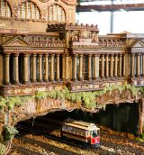 A model train driving under a model of Penn Station during the Holiday Train Show