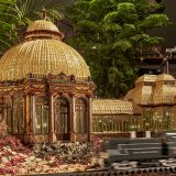 A train driving past a model of the Enid A. Haupt Conservatory at the Holiday Train Show
