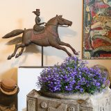 Image of bronze horse with woman rider and purple flowers in front on a stone pedstal