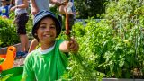 Young boy in blue hat and green shirt holding up a carrot with soil from the ground.