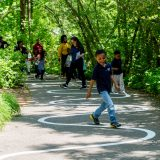 Children and parents following a winding path in the Everett Children's Adventure Garden.