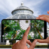 A hand holding a phone up in front of the Conservatory.