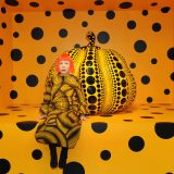 Yayoi Kusama seated in front of a giant black and orange polka-dotted pumpkin sculpture in a room of the same design.