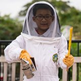 A boy in a beekeeping outfit.