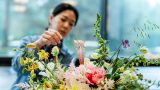 Photo of a woman creating a floral centerpiece