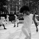 black and white image of people dancing in white clothing