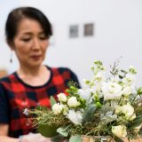 A student creating a white and green floral arrangement