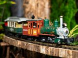 Close up of a silver and green train with red cars on a wooden train track