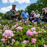 A Garden employee teaching a group of visitors about roses.