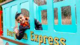 Photo of a child in a blue play train