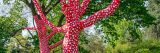 Trees wrapped in red fabric with white polka dots. More unwrapped trees and bushes can be seen in the background.