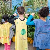 Three children's backs wearing hand made capes for being plant champions