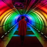A person walking through a tunnel illuminated by a rainbow of lights.